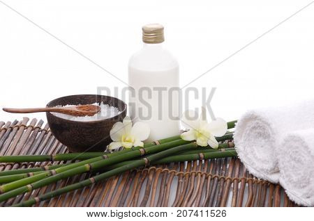 Spa setting withroller towel ,orchid, oil,bamboo grove,salt in bowl  on mat