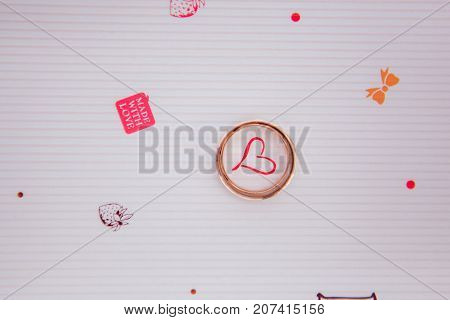 Wedding two gold rings on the white background with hearts painted. Made with love
