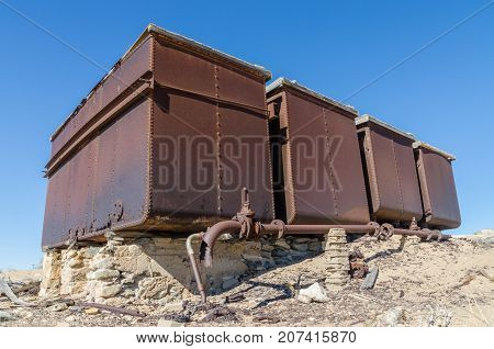 Rusting water tank at ruins of once prosperous German mining town Kolmanskop in the Namib desert near Luderitz, Namibia, Southern Africa.