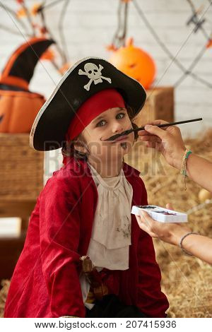 Little boy having his face painted for Halloween celebration