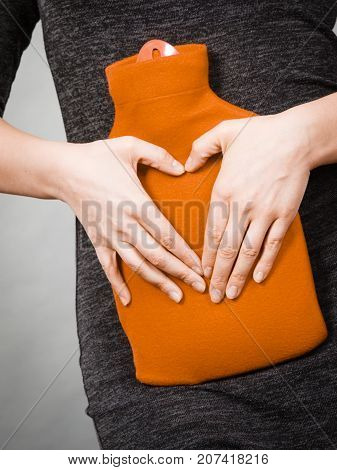 Girl Holds Hot Water Bottle On Belly Making Heart Shape By Hands