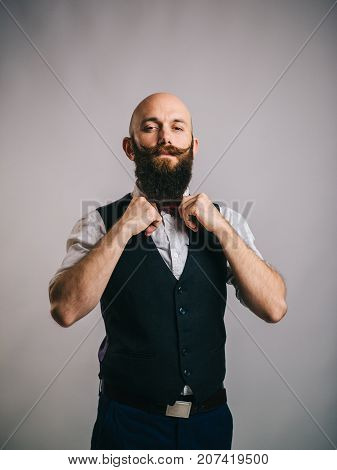 charismatic bearded man corrects a bow tie on a gray background