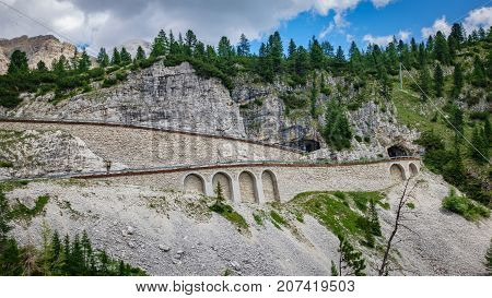 Wide angle view of Falzarego pass curve with tunnel, profile view