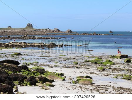 BREST, FRANCE, JULY 28 2017: View of the rocky shoreline and lovely golden sand beach at La Greve Blanche, Plougerneau, near Brest in Britttany France. Brittany is a hugely popular tourist destination
