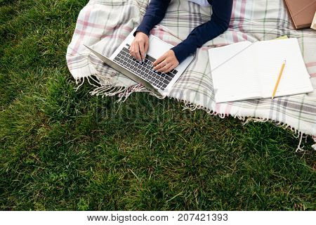 Top view of a female student studying on laptop computer while lying on the grass with a textbook