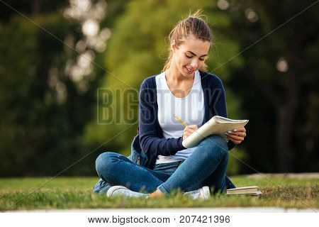 Portrait of a joyful smiling student girl with backpack writing in textbook while sitting on the grass at park