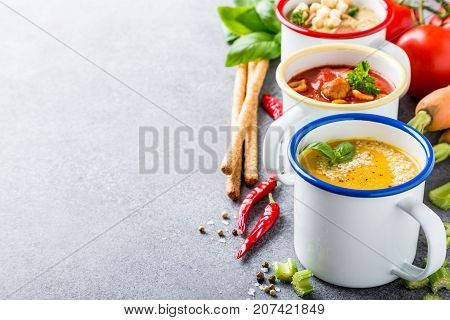 Assorted delicious homemade soups in enamel mugs with ingredients. Healthy food concept with copy space.