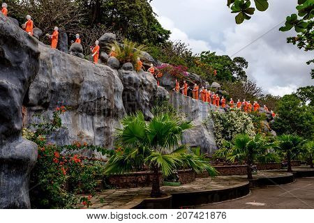 Sculptures of buddhist monks at cave temple in Dambulla, Sri Lanka. Cave temple has five caves under a vast overhanging rock and dates back to the first century BC.