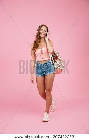 Full length portrait of young cheerful readhead woman with backpack, listening to music in white headphones, looking away, over pink background