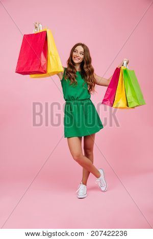 Portrait of young smiling readhead woman in green dress, holding colourful shopping bags, isolated over pink background