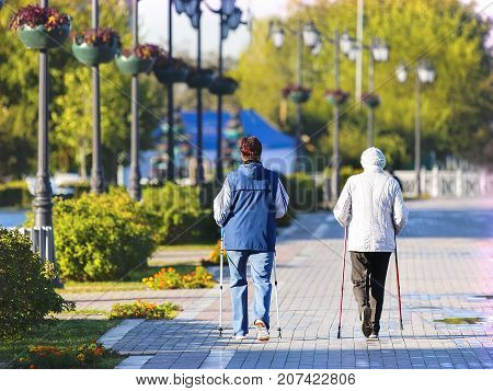Two elderly women with sticks for Nordic walking on the background of the city waterfront