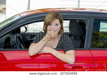 female rookie new driver young beautiful woman scared and stressed while driving car in fear and shock face expression in stress and confusion after crashing