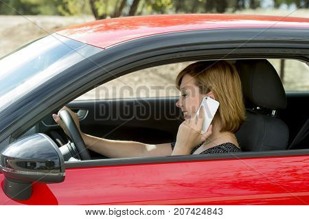 young beautiful and attractive woman talking happy on mobile phone while holding car steering wheel driving distracted in risk of traffic accident by distraction and irresponsible use of telephone