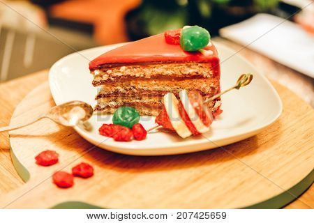 Cake with red glaze and candied fruits. Nut cake, pie. Teatime, cozy atmosphere. Nice artistic photo of fresh pastry for design, magazines, shop, cafe, menu, articles, restaurant, posters, calendars.