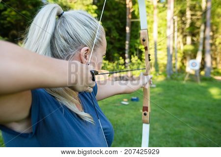 Female Archer Aiming Arrow At Target Board In Forest