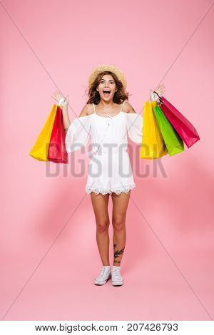Full length portrait of a happy excited girl showing shopping bags while standing isolated over pink background