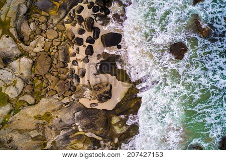 Aerial view looking down at sea waves hitting rocks of a beach on Lofoten islands in Norway