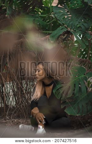 girl sitting in jungles. huge leaf around woman. she look is sexy. black jeans and blouse.