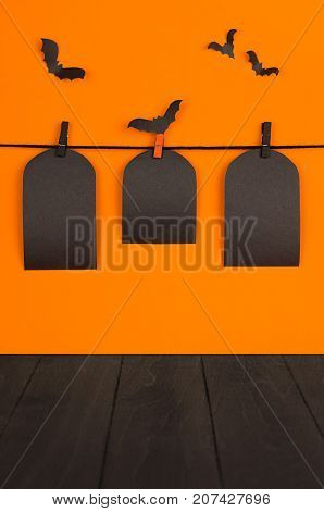 Halloween orange mock up background. Blank black sale labels tomb hanging on clothespins flock bats and wooden board shelf. Template for advertising design cover.