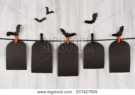 Halloween advertising mock up. Blank black sale labels tomb hanging on clothespins flock bats and white wooden plank background. Template for design cover.
