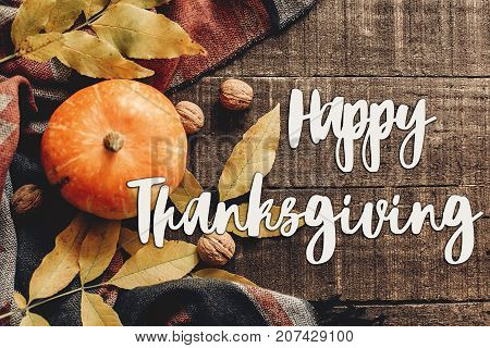 happy thanksgiving text sign flat lay. pumpkin with leaves and walnuts on stylish scarf top view space for text. seasonal greetings autumn fall holidays. harvest time. cozy mood