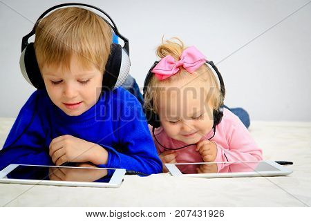 little boy and girl with headset looking at touch pad, modern technology