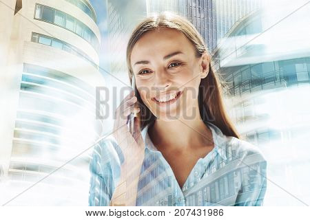 Fascinating news. Cheerful beautiful woman having pleasant discussion on the mobile phone while expressing delightful emotions