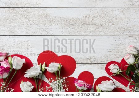 Top view of beautiful flowers on red hearts over vintage wooden table. Valentineâ??s day with white roses over red hearts. High angle view of white and pink roses on light wooden background.