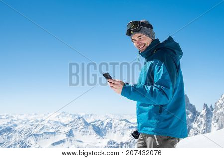 Happy man using smartphone in snowy mountains after skiing. Smiling guy texting phone message with copy space. Cheerful sporty man enjoy winter vacation at mountain with cellphone.
