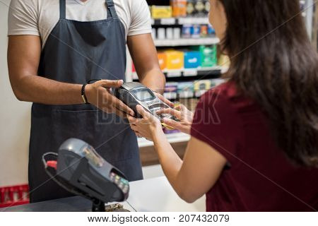 Close up of womanas hand using credit card swiping machine to make payment. Woman entering credit card code in a card reader machine. Woman pay to cashier with credit card at shop.