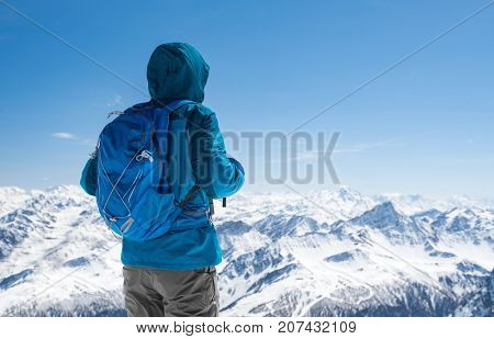 Rear view of sporty hiker man looking snowy landscape from mountain peak. Back view of man with backpack standing with copy space. Climber thinking while looking at a snowy winter landscape.