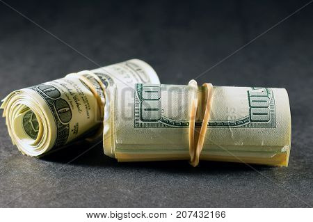 Money rolls, American dollars on dark surface and background. Horizontal image.