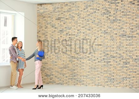 Female realtor and young couple buying new flat