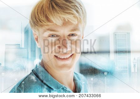 Lovely glance. Close up of positive handsome man smiling at you while expressing cheer and happiness