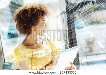 Sunny day. Happy diligent student putting down important information while holding notes in hands and looking at the distance
