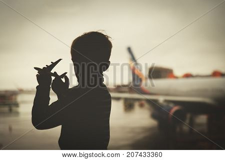 boy playing with toy plane while waiting in airport, travel concept