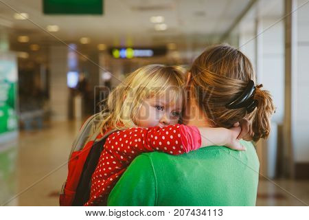 mother hugging little daughter before leaving on long trip, parting concept