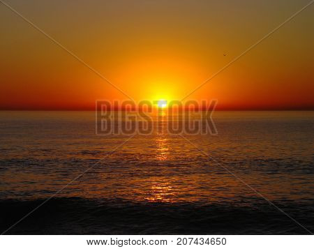 SUN SETTING UNDER A GOLDEN RED SKY OVER THE HORIZON OF THE ATLANTIC OCEAN, NEAR CAPE TOWN, SOUTH AFRICA