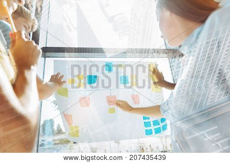 Sounds smart. Group of creative coworkers talking about business plan while putting color sticky notes on the paper and being attentive