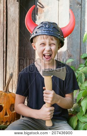 Boy in a Viking helmet with horns holds an ax outdoors pumpkin halloween in the background