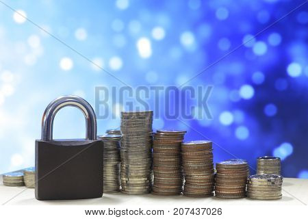 Coin money stack and lock, on blue light background. Saving and financial security concept.