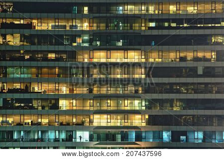 Late night at office . Multi-stories office building at night with worker working overtime. Lighting and working people within. Late night overtime in a modern office building