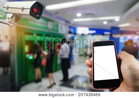 hand using smart phone and CCTV security indoor camera system operating with blurred image of people queuing to withdraw money from ATM e-bankingsurveillance security and safety technology concept