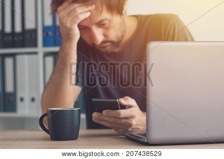 Worried freelancer reading bad news sms message on his smartphone in the office