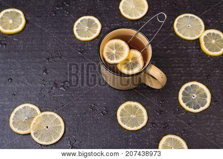 Big yellow mug with lemon tea and lemon circles on a black shabby background.