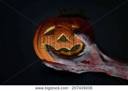 closeup of the scary hand of an undead man holding a carved pumpkin against a black background