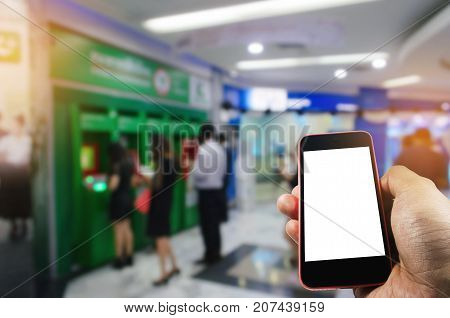 hand using smart phone isolated blank screen with blurred image of people queuing to withdraw money from ATM (Automated Teller Machine) e-banking finance payment and shopping online concept