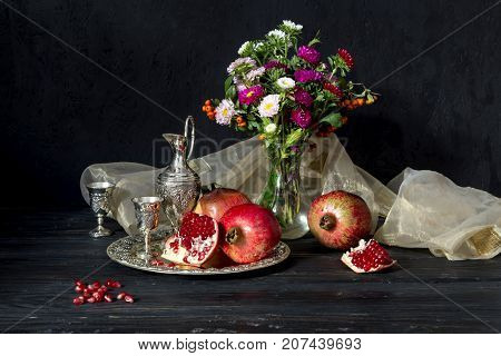 Still-life with a pomegranate, a jug, stemware and flowers in a vase on a wooden table close-up
