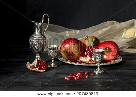 Still life with a pomegranate, a jug and a stemware of wine with a liqueur on a wooden table close up