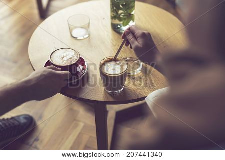 Top view of two people holding a nicely decorated latte art coffee cups enjoying their morning coffee. Selective focus on the left cup of coffee